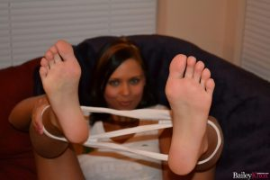 She's lifting her legs to show her bare feet